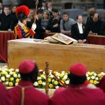 Bishops pay their respects near coffin
